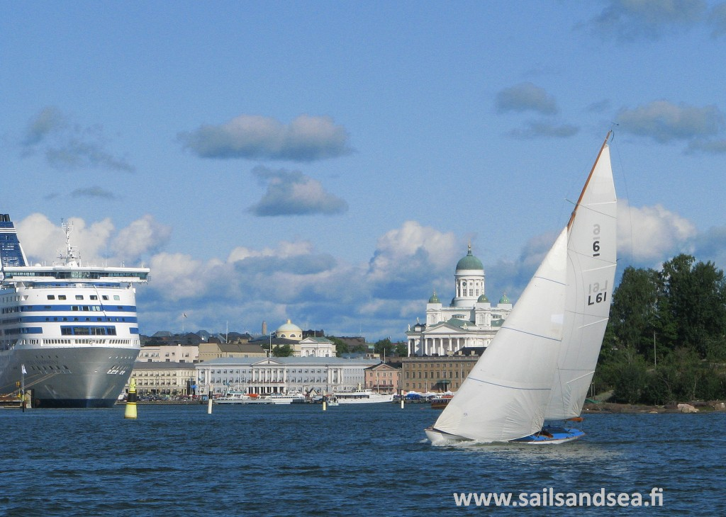 Sailing boat underway with buildings and cruise ship inthe background