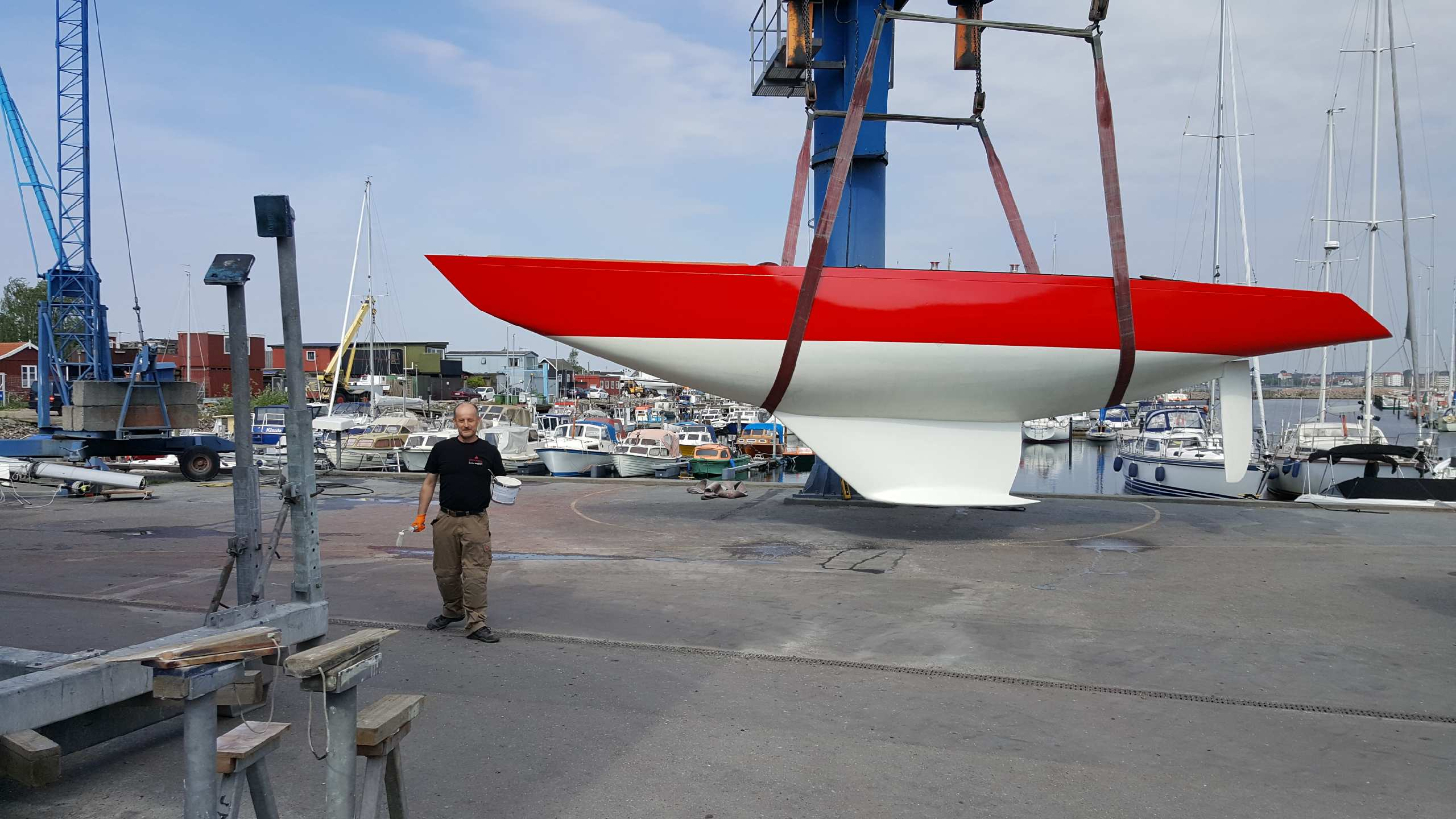 Red sailing boat on a crane