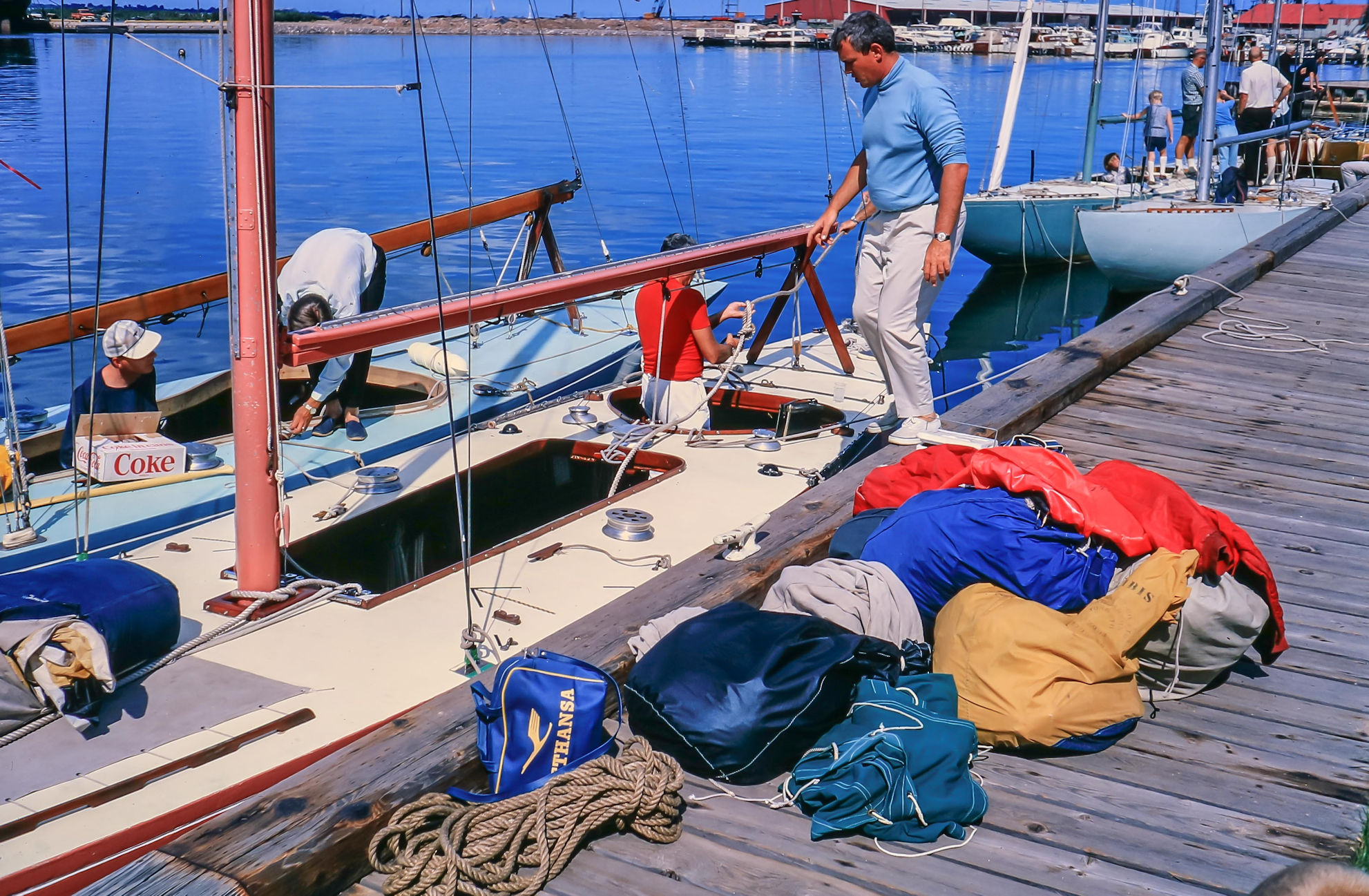 Boats alongside a pontoon. Sail bags and belongings are on the potoon.
